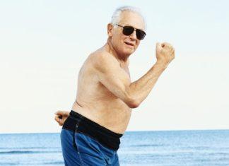 glad ældre mand i badebukser flekser muskler